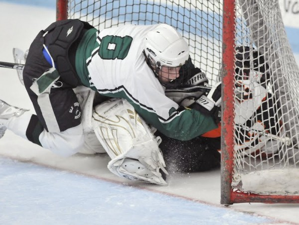 Old Town forward David Wilcox (8) draws a &quotcharging&quot call for hitting Brewer goalie Patrick Spaulding in the first period of their game in Orono on Monday, Jan. 23, 2012.