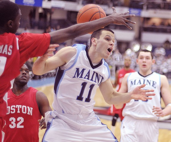 Maine men's basketball player Andrew Rodgers (11) gets stripped of the ball by Boston University player Malik Thomas (31) in the first half of their game in Orono on Wednesday, Jan. 11, 2012.