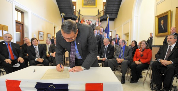 Maine Gov. Paul LePage signs &quotA Call to Prayer for Maine&quot during a ceremony in the Hall of Flags at the Maine State House in Augusta on Tuesday.