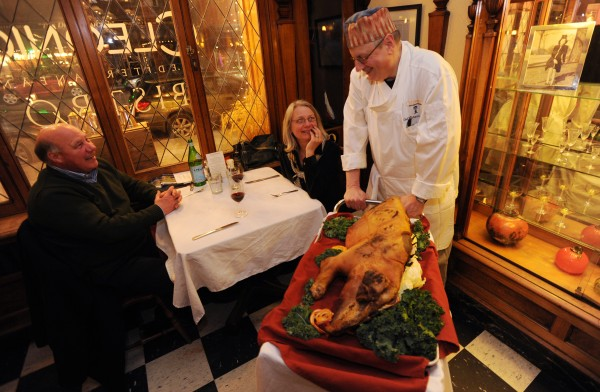 Chef Rich Hanson wheels a roasted pig on a cart past dinners at Cleonice in Ellsworth on Sunday, Jan 29, 2012. Hanson and his wife Cary put on a dinner styled after the movie &quot Big Night&quot once a year, this is their fifth year creating the event.