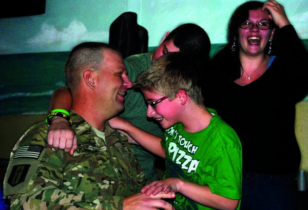 Thirteen-year-old Joshua Mariello hugs his father, Richard Mariello, Friday night at the Old Orchard Beach High School cafeteria. His brother, Jeremiah Mariello, and sister, Bobbie Elwell, are also pictured welcoming their father home from a year-long deployment in Afghanistan.