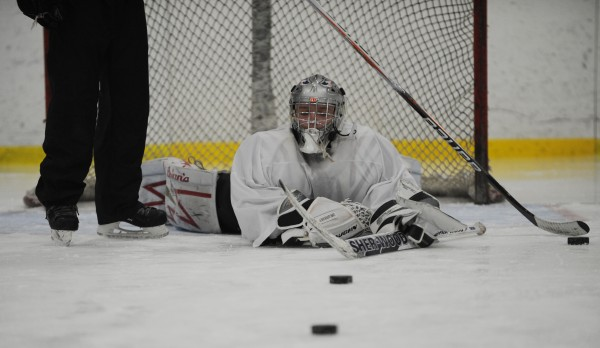 Goalie student Josh Delp of Bangor lays on the ice infront of the goal at Sawyer Arena on Monday, Jan. 2, 2012 as instructor Justin Climo removes pucks from the goal.