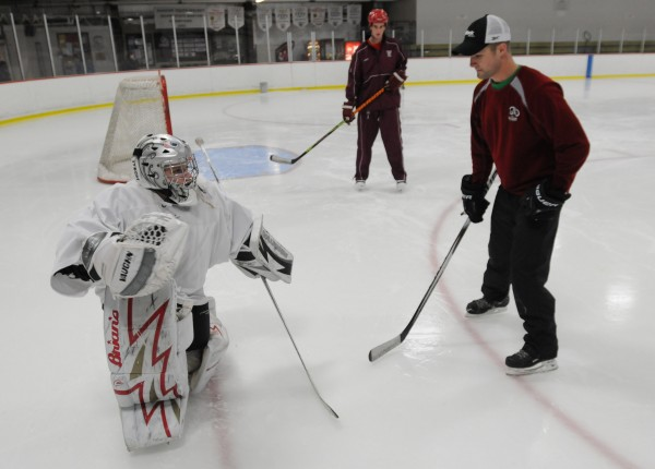 Goalie student Josh Delp, left, of Bangor gets a lesson from goalie instructor Justin Climo, right, at Sawyer Arean on Monday, Jan. 2, 2012, as assistnant Chris Howat, center, watches.