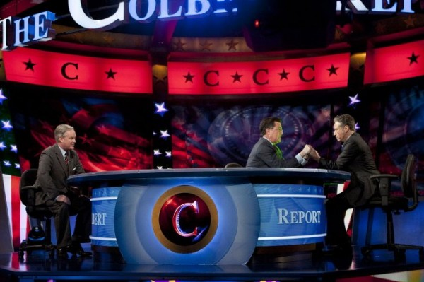 Stephen Colbert, center, and Jon Stewart, right, hold hands during The Colbert Report, as Trevor Potter looks on Thursday in New York. During the episode, Colbert legally transferred his super political action committee to Stewart, his friend and Comedy Central cohort.