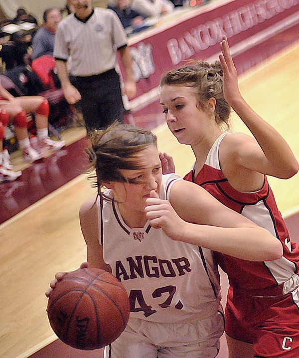 Bangor girls basketball player Mary Butler (42) muscles her way past Cony player Josie Lee along the baseline in the first half of their game in Bangor, Maine, Friday Jan. 6, 2012.