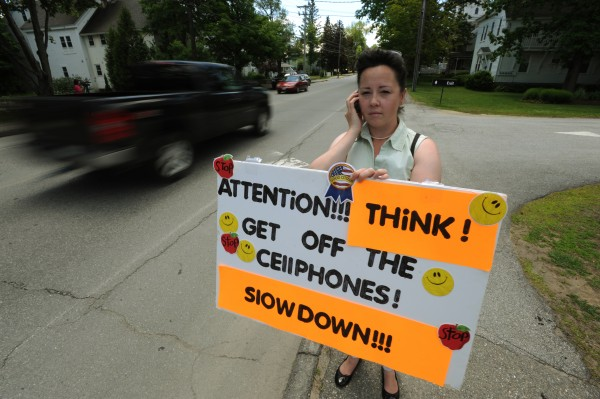 University of Maine student Sylvia Schuler, 36, holds a sign for traffic to see along Main Street in Orono in June 2009. Schuler, a part-time crossing guard, witnessed a dog being run over and said people often drive while distracted. She and fellow crossing guard Charity Lawrence (not pictured), 20, asked drivers to put down their cellphones and pay attention to their driving.