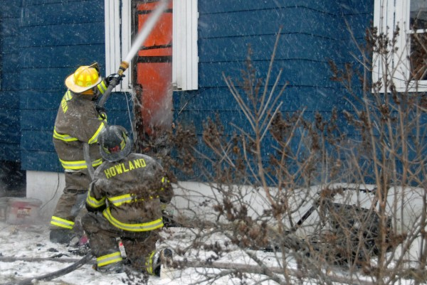Firefighters from five northern Penobscot County towns fought fire and blizzard conditions but were unable to save from destruction a 1 1/2-story house and attached garage at 91 Old County Road in Enfield on Thursday, Jan. 12, 2011.