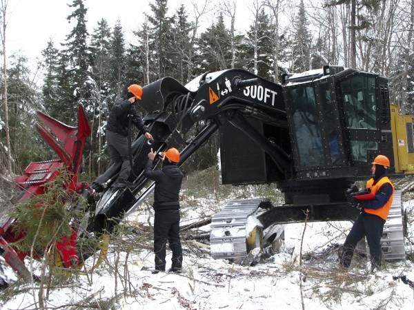Covered head-to-toe while filming outside in January in the North Woods, cameramen Chung-Wei Yi (far left) and Erin Harvey tape a small camera to the boom of a feller buncher working on land owned by The Nature Conservancy in far northern Somerset County.
