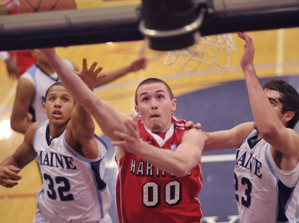 Hartford men's basketball player Wes Cole (00) gets an easy 2 points past Maine players Gerald McLemore (32) and Kilian Cato (23) in the first half of their game in Orono, Maine, on Thursday, Jan. 19, 2012.
