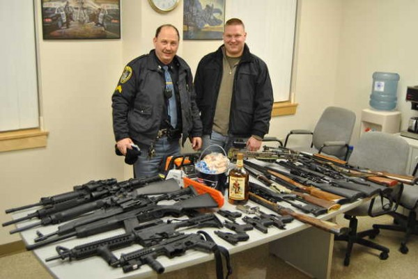 Jay police Cpl. Jeffrey Fournier (left) and Detective Richard Caton IV stand next to a table with 22 guns, a laptop, a bottle of rum, a chain saw and a bucket of change that police reportedly recovered Friday night at a North Jay residence.