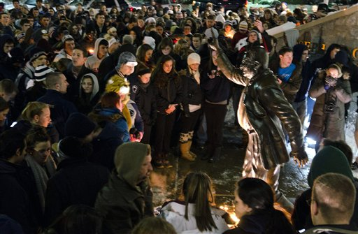 People gather at a statue of former Penn State football coach Joe Paterno in State College, Pa, on Saturday, Jan. 21.