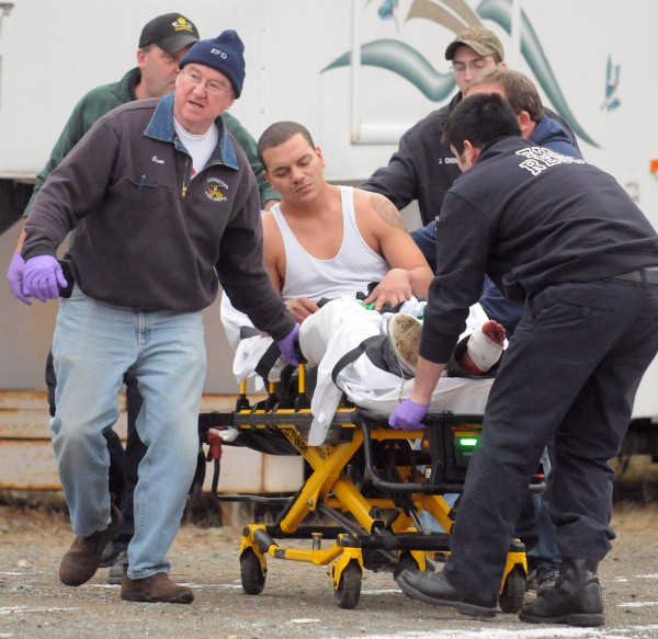 Darren Seidell is taken to an ambulance from an Eddington home Saturday afternoon. He had a bandage on his left foot and was assisted by first responders when he was escorted from the house.