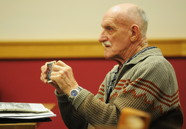 Raymond Phelps of Palmyra shows a photograph of his house located at 116 Oxbow Road in Palmyra to Judge Peter Darvin during his initial court appearance in Skowhegan on civil charges related to unauthorized additions to his home.