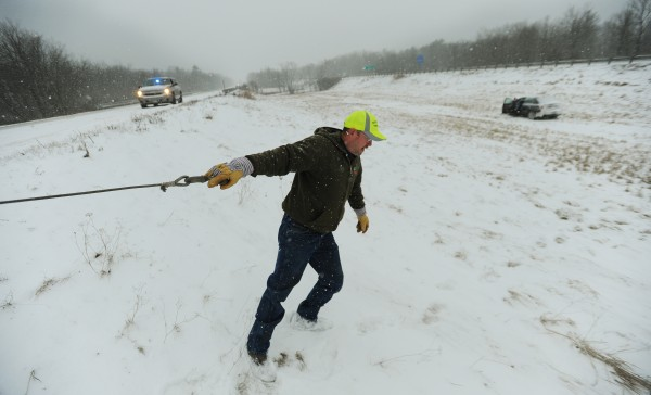 Andy Dunn pulls a cable from a wrecker along Interstate 95 northbound in Hampden on Thursday, Jan. 12, 2012 in order to assist a waiting motorist that spun in to the median due to the snow-covered highway.