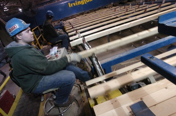 Chris Lowery (foreground) and Shawn Lyons, graders at Pleasant River Lumber in Dover-Foxcroft, inspect freshly cut two-by-fours as the wood makes its way along a conveyor in December 2007.