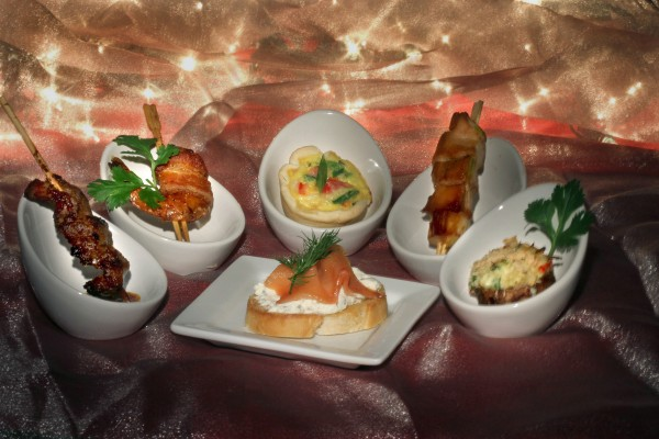 Pasilla marinated flank steak (from left), bacon-wrapped shrimp, ham and cheese mini quiche, yakitori chicken, crab-stuffed mushroom caps, and herbed cheese crostini with smoked salmon (center) can all help make a winter gathering tasty.