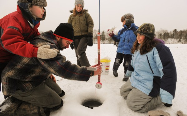 T.J. Schaefer (center left) and Susan Best (center) brought their kids Ethan (left) Lauren (right) and Christian to the Maine Youth Fish and Game association's annual  family ice fishing day on Pickerel Pond in Township 32 for the third year. T.J. was resetting one of the tip-ups shortly after a fish got away.