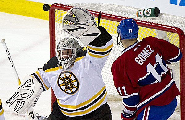 Boston Bruins goalie Tim Thomas (left) reaches up to glove the puck as Montreal Canadiens' Scott Gomez looks for a rebound during the  second period of an NHL hockey game on Wednesday, Feb. 15, 2012, in Montreal. The Bruins won 4-3 in a shootout. (AP Photo/The Canadian Press, Paul Chiasson)