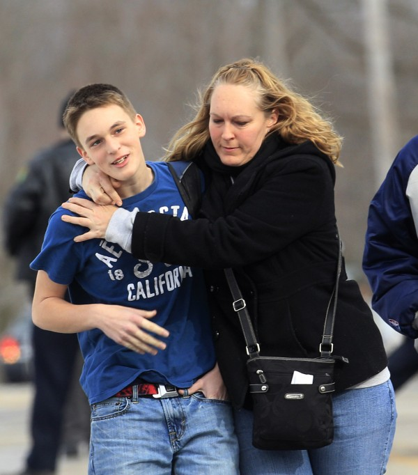 Doug Gasper, a ninth grader at Chardon High School, is hugged by his mother,  Sandy, as they leave Maple Elementary School Monday, Feb. 27, 2012, in Chardon, Ohio. Students assembled at Maple Elementary School after a shooting took place at the high school.  A gunman opened fire inside the high school's cafeteria at the start of the school day, wounding four students, officials said. A suspect is in custody.