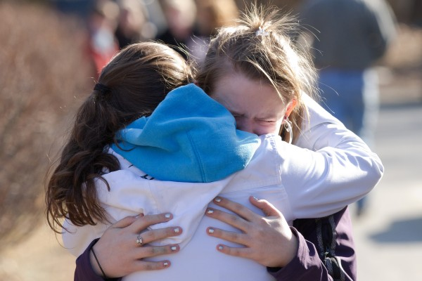 An unidentified student is comforted outside Walpole Elementary School where a 14-year-old male student shot himself in front of many classmates in the school's cafeteria in Walpole, N.H., on Friday, Feb. 10, 2012.  Police are investigating the shooting, which they say was self-inflicted.