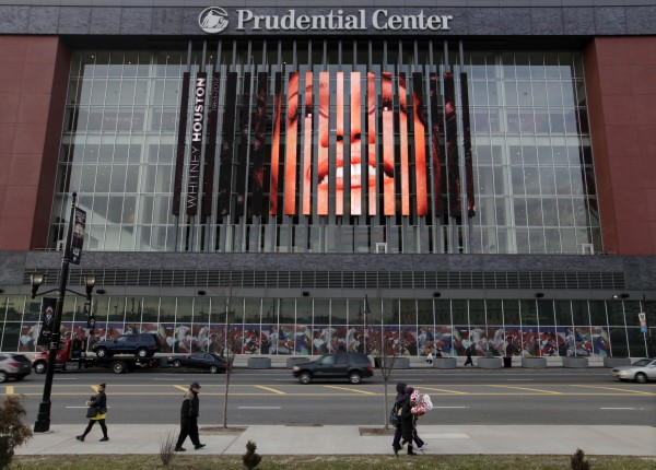 People walk past a large image of Whitney Houston displayed on the side of the Prudential Center in Newark, N.J., Tuesday, Feb. 14, 2012. Houston's funeral will be held Saturday in the church where she first showcased her singing talents as a child, her family choosing to remember her in a private service rather than in a large event at an arena.