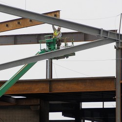 Workers in their safety harnesses carefully position a crane-hoisted roof beam into place atop the new Bangor Arena on Friday morning, Feb. 24, 2012. With the help of unseasonably warm weather, the arena construction remains on schedule.
