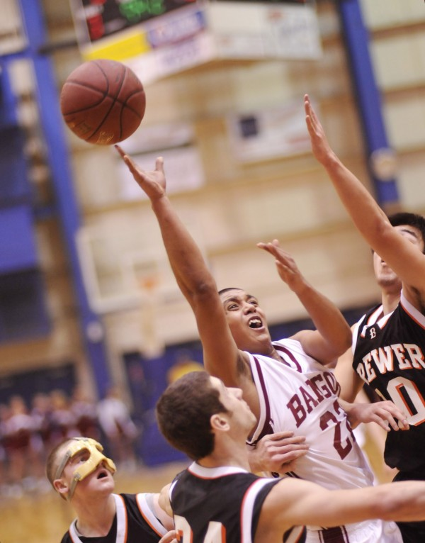 Bangor boys basketball player Xavier Lewis (22) drives into the paint under pressure from Brewer players Yuhi Sasaki (right) and Matt Cuskelly (front) in the first half of their game in Bangor, Maine, Thursday, Feb. 9, 2012.