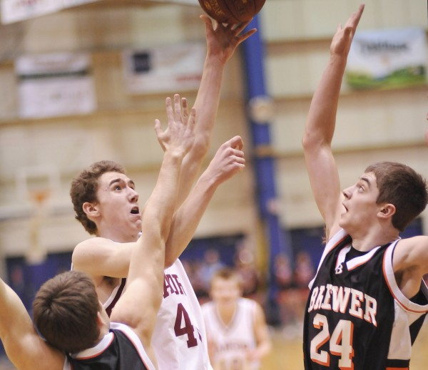 Bangor boys basketball player Zeek Clark (40) drives to put up a shot over Brewer players Ian Burgess (24) and Nate Morris (front) in the first half of their game in Bangor, Maine, Thursday, Feb. 9, 2012.