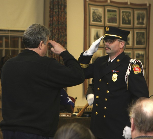 Retiring Fire Chief Jeff Cammack (left) receives a salute from Capt. Troy Lare of the Bangor Fire Department at a City Council meeting Monday, Feb. 27, 2012, in Bangor, Maine.