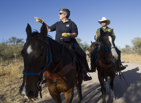 In this Oct. 30, 2011, file photo Homeland Security Secretary Janet Napolitano, left, tours the U.S.-Mexico border with Border Patrol agent Steve Venditouli in the Coronado National Forest near Nogales, Ariz. Most illegal border crossers are apprehended along the 2,000-mile long Mexican border in California, Arizona, New Mexico, and Texas.
