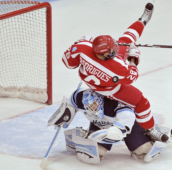 Maine goalie Dan Sullivan tries to keep his eyes on the puck as he is tackled by Boston University's Evan Rodrigues (26) in the first period of their game in Orono, Saturday, Dec. 10, 2011.