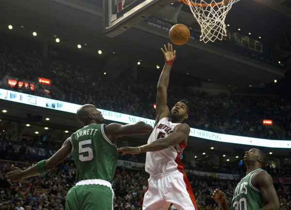 Amir Johnson of the Toronto Raptors lays the ball up as  Kevin Garnett of the Boston Celtics and Brandon Bass look on during the second half of play in Toronto on Friday, Feb.10, 2012.