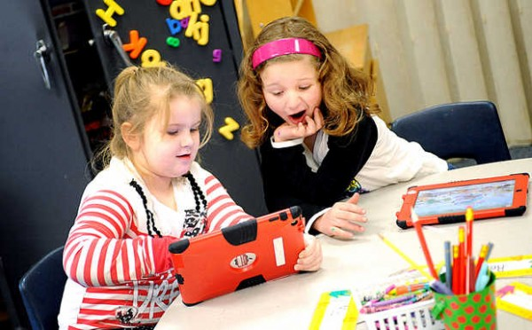 Mia Burgess, left, shows Rebecca Noone something on her iPad in Susan Lemeshow's kindergarten class at Sherwood Heights Elementary School on Wednesday.