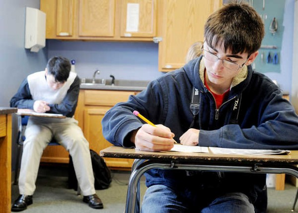 Sophomores Jia Jun Lam, left, of Lisbon and James Morrill of Bowdoin prepare for the SAT at the Vineyard Christian School at 9 Foss Road in Lewiston on Wednesday. The prekindergarten through grade 12 school will close at the end of this school year.