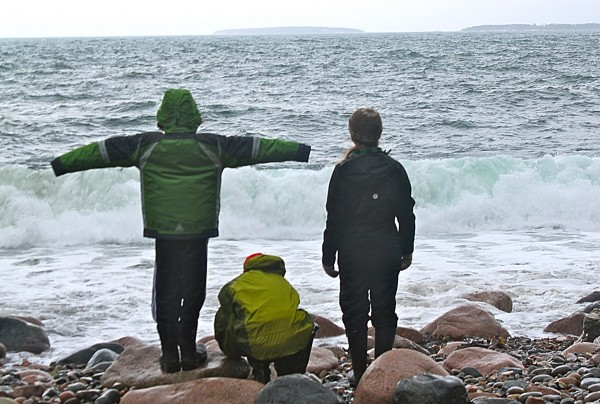 Robert Denegre (from left), 11, of Bar Harbor stands with his arms outstretched beside Emerson Jeffery, 11, of Bar Harbor and Lucy Atkins, College of the Atlantic senior and organizer of the &quotNatural History Exploration&quot vacation camp on Feb. 23, 2012, on Hunter's Beach on Mount Desert Island.