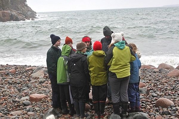 Eight campers gather on Hunter's Beach on Mount Desert Island on Feb. 23, 2012, with College of Atlantic senior Lucy Atkins and COA junior Anne Cohen, who together are leading a vacation camp for middle schoolers, &quotNatural History Exploration,&quot for February school vacation. Atkins organized the camp for their senior project.