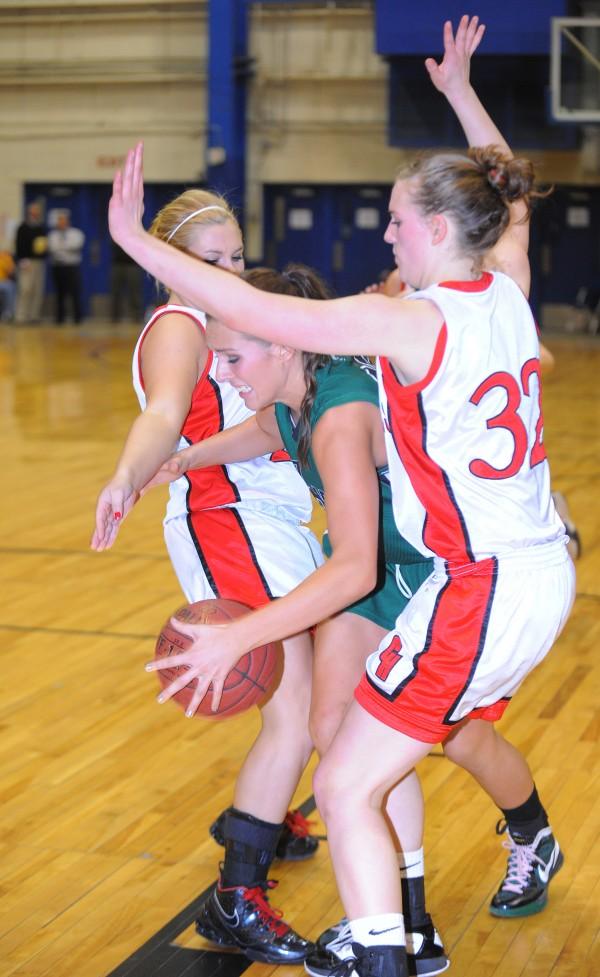 Old Town High School's Ashley Abbott (center) drives for the basket between Camden Hills High School's Jordon Knowlton (right) and Sarah Steele during the second half of a Class B quarterfinal game at the Bangor Auditorium Friday evening.