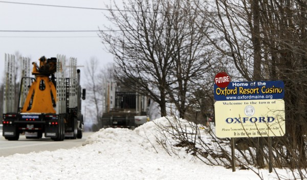 Truckers pass a sign for The Oxford Casino, which is under construction and is scheduled to open this summer, in Oxford, Maine, on Monday, Feb. 27, 2012.  The casino will hold a job fair Saturday in Oxford where it is seeking applicants to fill more than 50 open positions as table games dealers.
