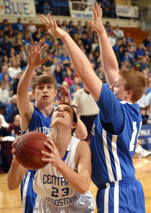 Central Aroostook's Steven Decker eyes the the rim through the heavy Mariner defense of Tim Cormier (left) and Connor Morey (right) during their Class D semifinal game at the Bangor Auditorium on Thursday.