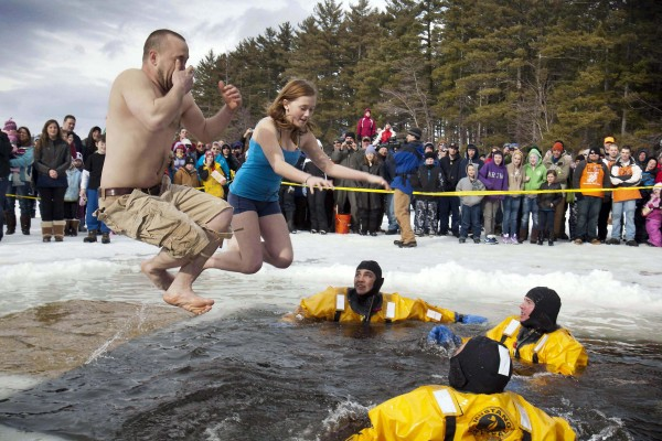 Ryan Carson and his daughter, Skylar, 12, of Gray, jump into the icy water during the Crystal Lake Ice Fishing Derby, Saturday, Feb. 25, 2012, in Gray. Polar Plunge participants raised about $10,000 to benefit the USO, the Department of Inland Fisheries and Wildlife and the Patriot Parents.