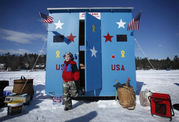 Matthew Nile, 8, of Harrison, exits Josh Laird's ice fishing shanty during the  Crystal Lake Ice Fishing Derby, Saturday, Feb. 25, 2012, in Gray. A competition was held for the shanty with a best patriotic theme.