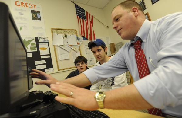 Deer Isle-Stonington High School Principal Todd West (right) visits a technology class in 2010 to work with Alec Eaton (left) of Deer Isle and Curtis Weed of Stonington as they created a map of Maine public schools.