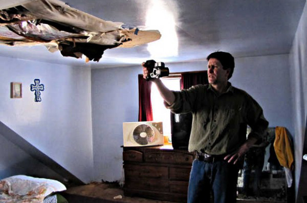 DeWitt Kimball of Complete Home Evaluation Services in Brunswick uses an infrared camera to capture images of heat loss in the house of Robert and Wilma Hartford of Peru on Sunday. Kimball offered his services to the couple to help cut their dependency on oil, after he learned of their struggle in an article the The New York Times on Saturday.