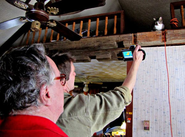 DeWitt Kimball, back, of Complete Home Evaluation Services in Brunswick, shows homeowner Robert Hartford of Peru how an infrared camera shows heat loss in his house.