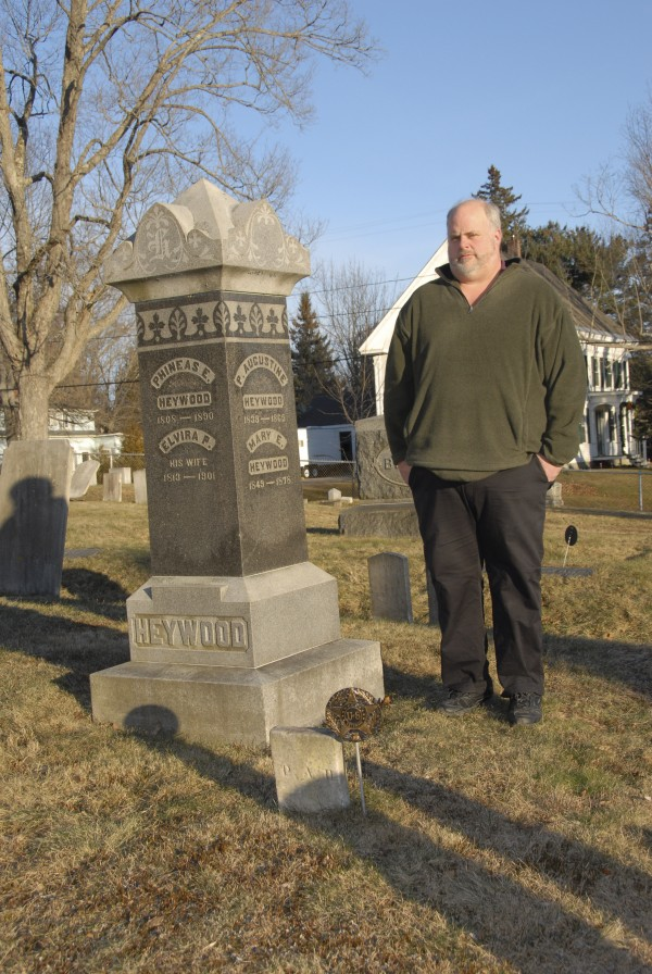 "Emeric Spooner, the librarian at Buck Memorial Library in Bucksport, stands at the grave of Phineas Augustine Heywood, a Civil War veteran buried at Oak Grove Cemetery in Bucksport. Spooner identified Heywood as a veteran while researching his new book ""Maine Gravestones and Flags Volume II: Honoring Our Civil War Heroes."""