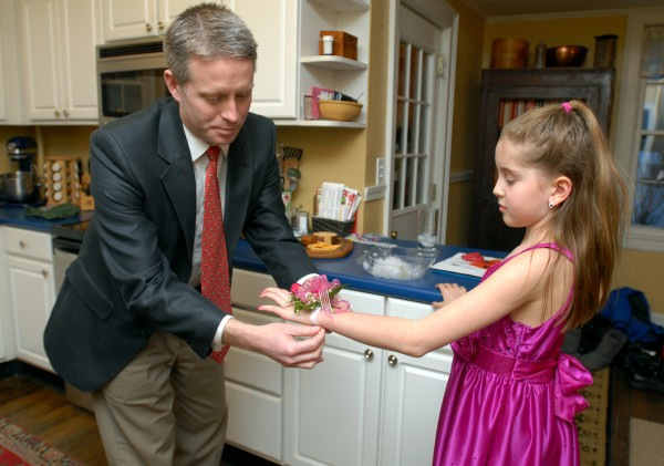 Charles Budd places a corsage on his 10-year-old daughter Elisabeth's wrist before leaving for the Father-Daughter Valentine's Dance at the Bangor Civic Center on Friday evening.