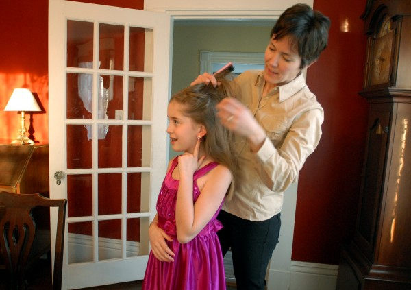 Mary Budd fixes her daughter Elisabeth's hair as she gets ready for the Father-Daughter Valentine's Dance on Friday evening.