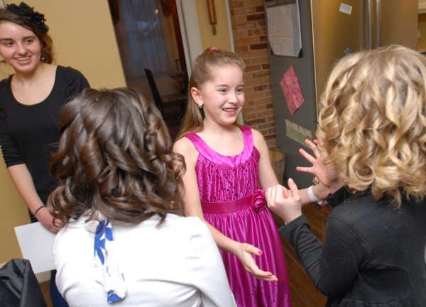 Elisabeth Budd, 10, admires her friends' hair as they arrive at her house before leaving for the Father-Daughter Valentine's Dance at the Bangor Civic Center on Friday evening.