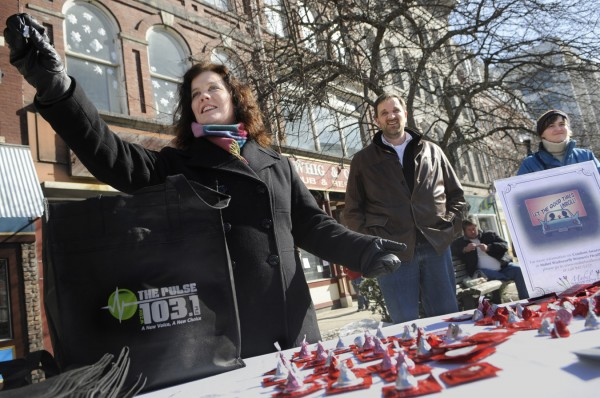 The Pulse (103.1 FM, 620 AM) Morning Show's Pat LaMarche (left) holds up a Hershey Kiss and she, radio co-host Don Cookson (center) and Mabel Wadsworth Women's Health Center education and outreach coordinator Abbie Strout (right) set up a booth in West Market Square in downtown Bangor to hand out some Valentine's Day freebies, including chocolate and condoms.