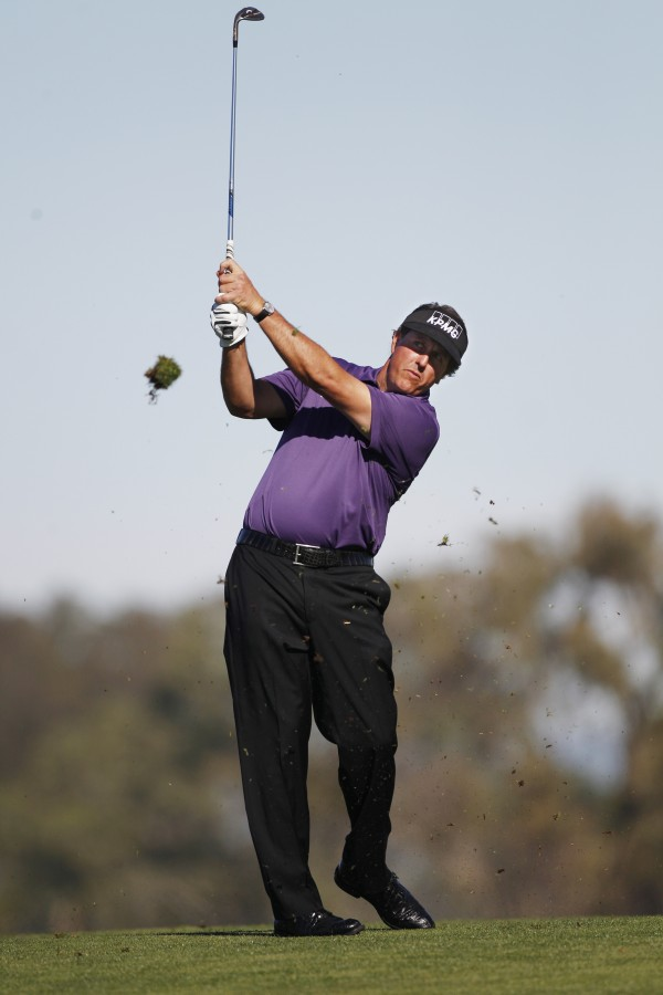 Phil Mickelson follows through with his short iron approach to the second green on the South Course at Torrey Pines during the opening round of the Farmers Insurance Open, Thursday, Jan. 26, 2012, in San Diego.